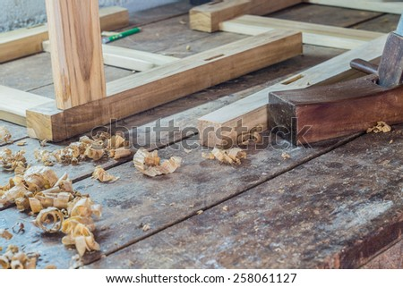 wooden plane in a workshop of the carpenter with curls of wood shavings - stock photo