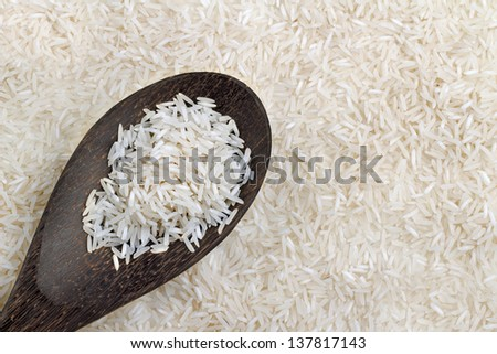 wooden spoon with basmati rice on background of rice - stock photo