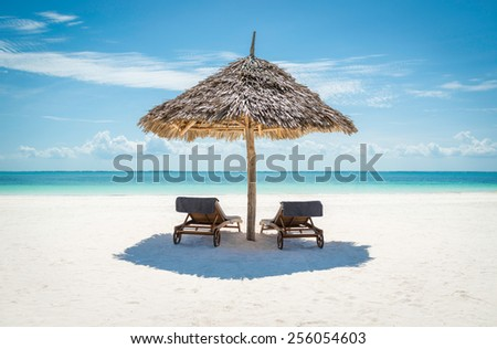 2 wooden sun loungers facing the tropical, turquoise blue Indian Ocean under a thatched umbrella on a white sandy Zanzibar beach - stock photo