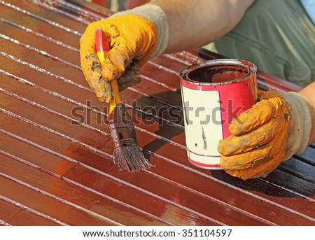 Worker painting new wooden door with paintbrush - stock photo
