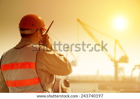 worker with large crane site and sunset background - stock photo