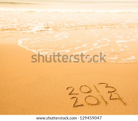2013 - 2014 written in sand on beach texture - soft wave of the sea. - stock photo