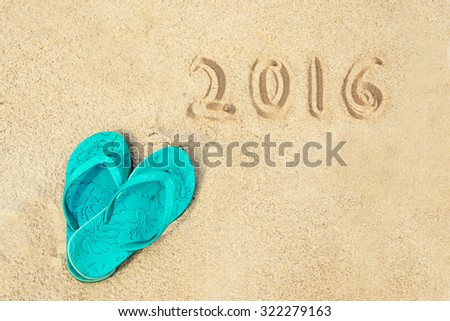 2016 written in the sand of a beach with flip flops - stock photo