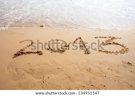 2013 written in the sand on the beach in summer - stock photo