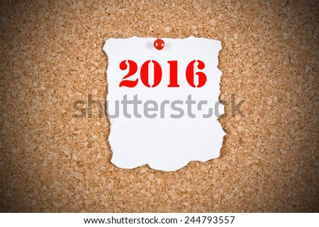 2016 written on a sheet with ragged edges mounted on cork billboard - stock photo