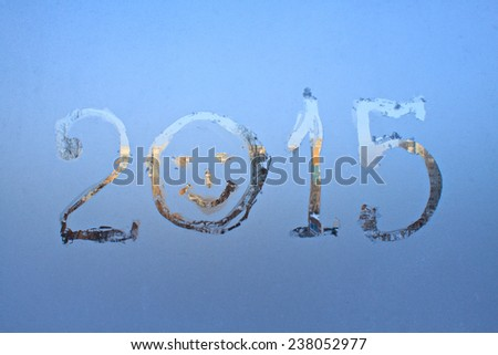 """2015"" written on frosty winter window background  - stock photo"