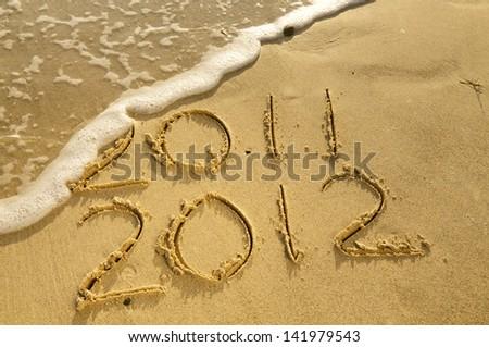 """""""2011 2012"""" written on sand. - stock photo"""