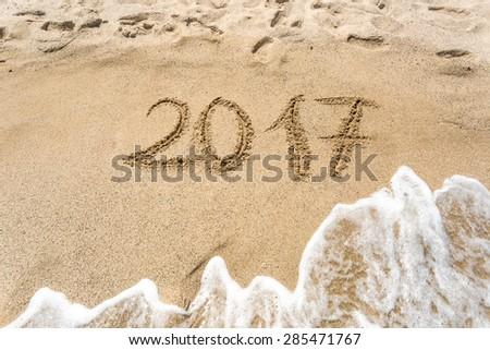 2017 written on sand beach at ocean - stock photo