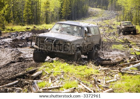 4x4 action through a huge mud bog. - stock photo