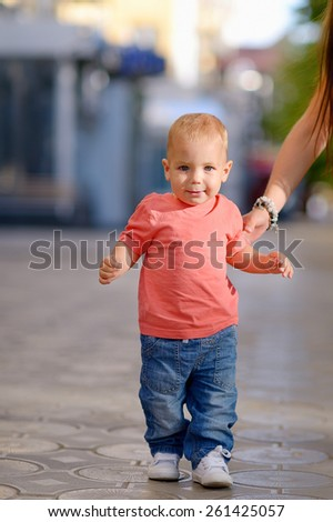 1 year baby, holding the hand of his mother, blond hair, gray eyes, a red shirt, blue jeans. Against the background of green trees. - stock photo