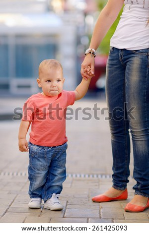 1 year baby, holding the hand of his mother, blond hair, gray eyes, a red shirt, blue jeans, mother in a white T-shirt, blue jeans. Against the background of green trees. - stock photo