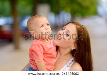 1 year baby in the arms of mother, blond, gray eyes, a red shirt, blue jeans, Mum young beautiful brunette with straight hair, a white T-shirt. Green trees. Young mother with her baby in her arms. - stock photo