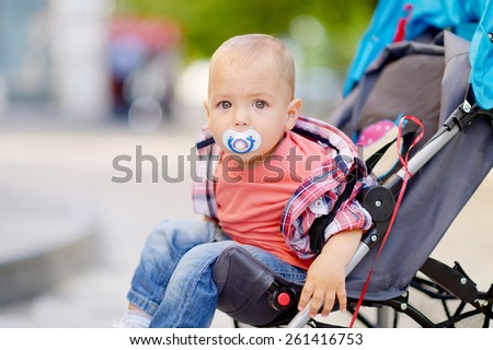 1 year baby sitting in the baby carriage, with a pacifier in his mouth, blond hair, gray eyes, a red T-shirt, plaid shirt, blue jeans, a city on the background of green trees. Baby with a pacifier. - stock photo