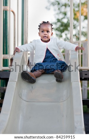 3-year old African American Girl Playing on slide in the Playground - stock photo
