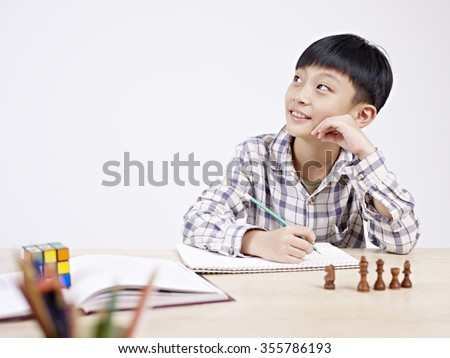 10 year-old asian elementary schoolboy looking away while studying. - stock photo