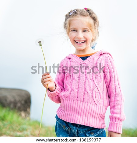 6-year-old beautiful girl holds in her hand dandelion - stock photo
