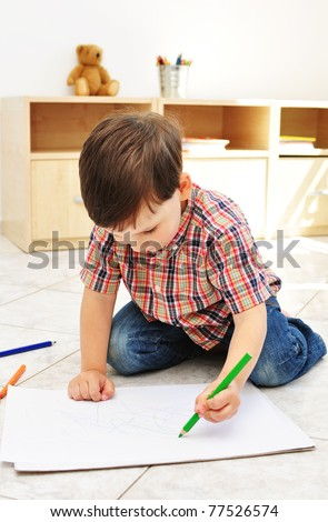 3-year old boy drawing in his room - stock photo