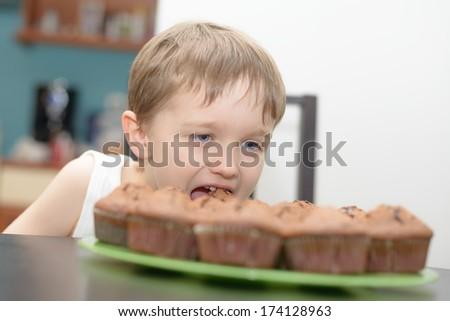 4 year old boy eats chocolate cake - muffin - stock photo