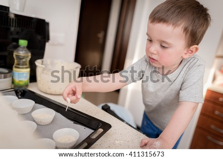 2 year old boy having fun preparing dough for muffins in kitchen at home - stock photo