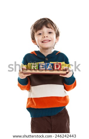 6 year old boy holding a book and blocks that spell read isolated on a white background promoting education - stock photo