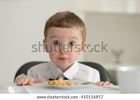 2 year old boy looking at camera with dessert cake on plate in front of him during family meeting. - stock photo