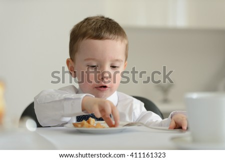 2 year old boy looking at camera with dessert cake on plate in front of him during family meeting - stock photo