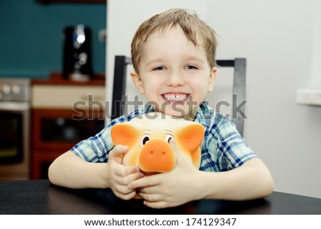 4 year old boy smiling and holding a piggy bank - stock photo