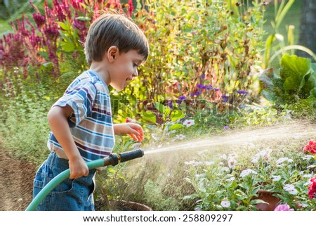 3 year old boy watering the garden with a hose in the summer - stock photo