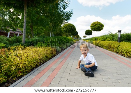 2 year old child in the park, in blue jeans and a white t-shirt. Blond boy with blue eyes. Cheerful child in the summer park. Laughing baby in nature. - stock photo