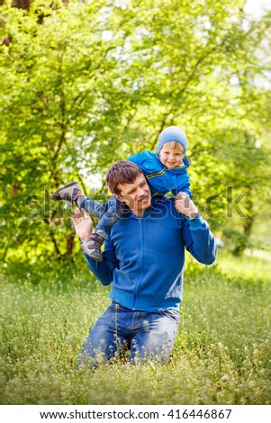 2-3-year-old cute boy dressed in a blue jacket and jeans having fun with his father on the green grass in the park. Spring warm day. Around the beautiful nature. Trees and lush green grass. - stock photo