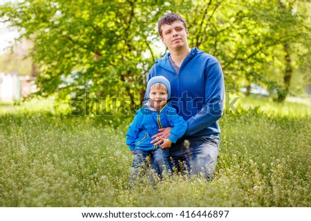 2-3-year-old cute boy dressed in a blue jacket and jeans sitting with his father on the  green grass in the park. Spring warm day. Around the beautiful nature. Trees and lush green grass. - stock photo