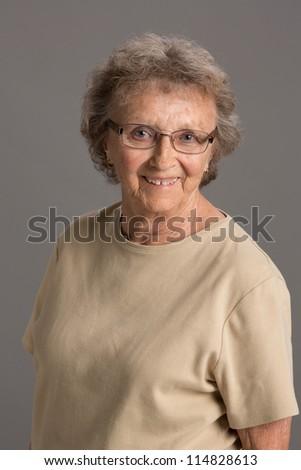 80 Year Old Elderly Senior Happy Portrait Headshot on Gray Background - stock photo