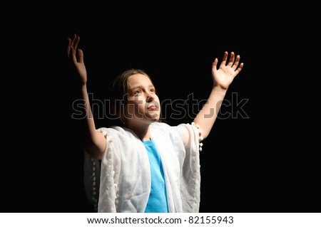 10 year old girl looking up on a black background as if  praying. - stock photo