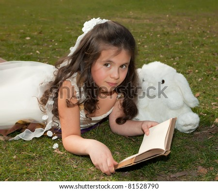 7 year old girl reading a book on grass - stock photo