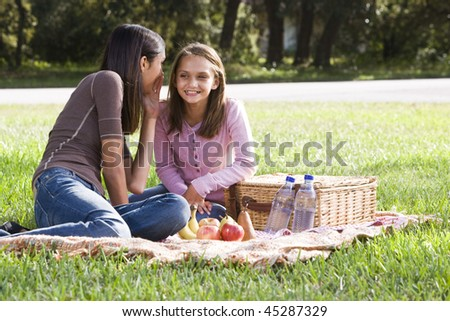 10 year old girl whispering to older sister while having picnic in park - stock photo