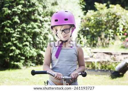 7 year old girl with bicycle with bike helmet and specs - stock photo