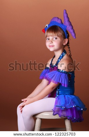 5 Year old girl with dancing costume on a brown background - stock photo