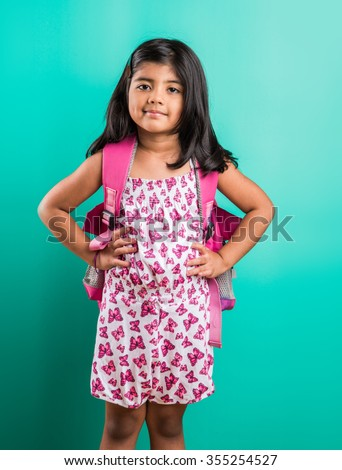 4 year old happy little indian girl standing with school bag on her back with casual dressing, isolated on green background, little asian girl with school bag, school bag and little girl - stock photo