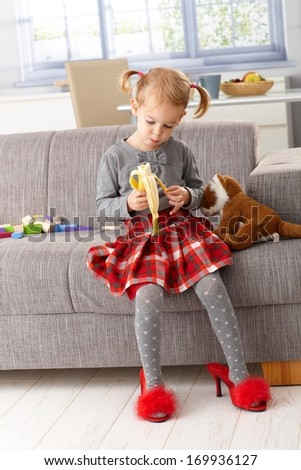 3 year old little girl eating banana at home, sitting on sofa, wearing high heel red slippers. - stock photo