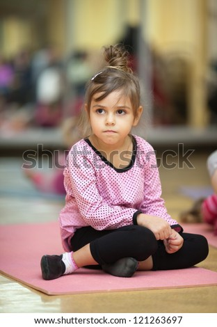 5 year old little girl sitting on the mat - stock photo