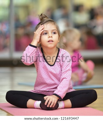 5 year old little girl sitting on the mat at dacing lesson - stock photo