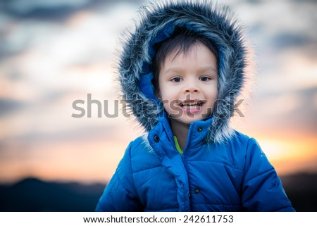 4 year old mixed race Asian Caucasian boy wearing a fur hooded winter coat in the mountains with dramatic sky and glowing sunset behind. - stock photo