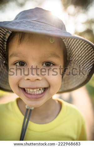 4 year old mixed race Asian Caucasian boy wearing a sun hat on a summer day - stock photo