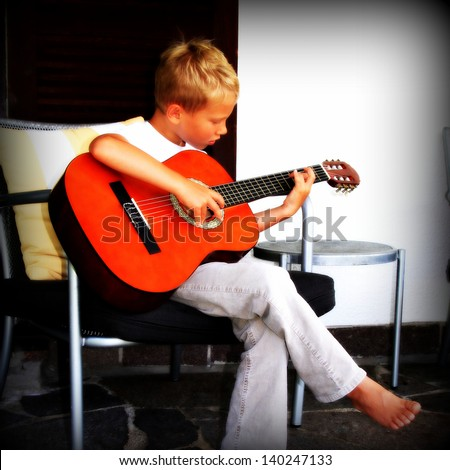 7 year old playing guitar - stock photo
