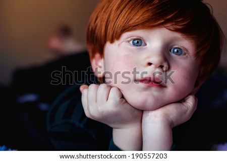 4 year old redheaded boy lying on a bed with his head resting in his hands--image taken indoors using natural light (Sparks, Nevada, USA) - stock photo