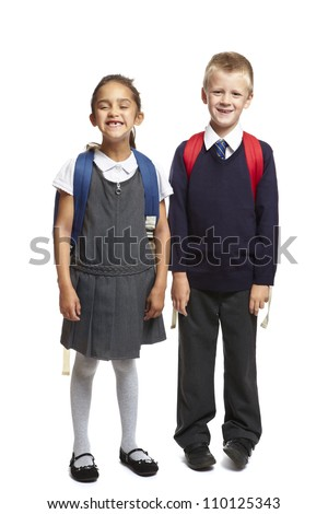 8 year old school boy and girl with backpacks smiling on white background - stock photo