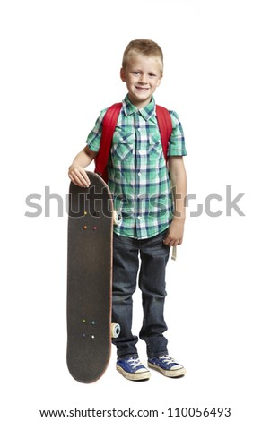 8 year old school boy with skateboard and backpack on white background - stock photo