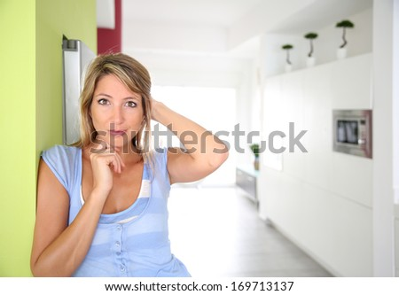 30-year-old woman standing in home kitchen - stock photo