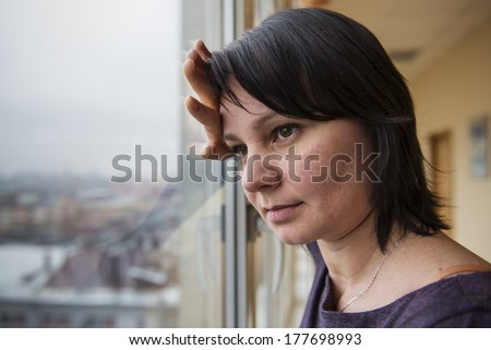 35 year old woman stands in front of the window. Real people series - stock photo