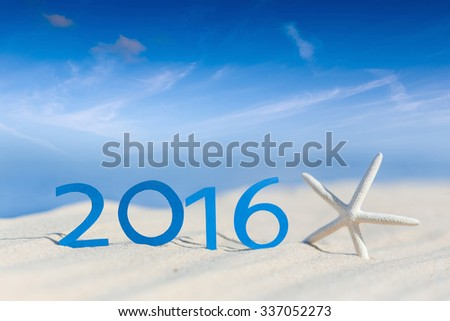 2016 year on a beach sand with starfish against the blue sky - stock photo